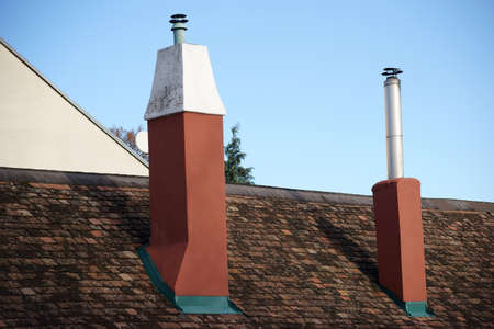 shingle: A shingle roof with two new chimneys and protruding stainless steel tubes. Stock Photo