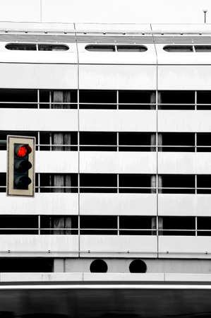 striking: A bus is passing a striking facade made of metal, in front of a red light. Stock Photo