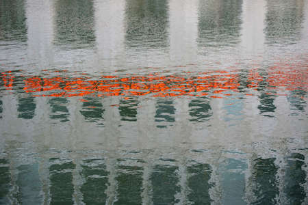 garish: The abstract reflection of a house with lights in the water.