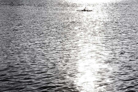 canoeist: A canoeist floats on a river of sparkling sunlight.