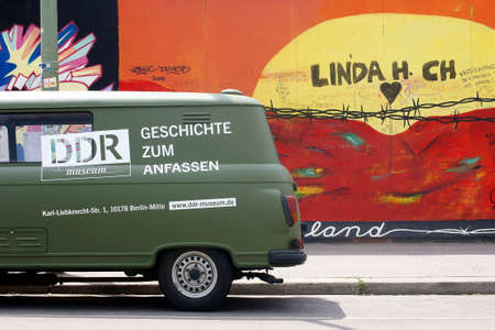ddr: Berlin, Germany - June 16, 2014: An old Barkas of DDR Museum is facing a work of art of the East Side Gallery on June 16, 2014 in Berlin. Editorial