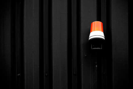 intensely: The photograph of a yellow warning light on an intensely colored corrugated iron wall. Stock Photo