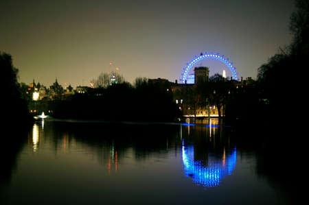 spiegelung: Beleuchtete Geb�ude sowie das Riesenrad London Eye der Stadt London hinter einem Teich w�hrend der Nacht.