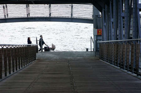 st pauli: Hamburg, Germany - September 21, 2014: A young family with a stroller goes to a harbor promenade and the Landungsbrcken on 21 September 2014 in Hamburg along.
