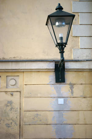 wall lamp: A nostalgic wall lamp and lantern on a prominent wall.