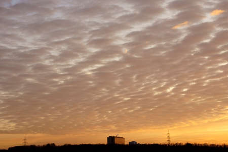 cloud formations: A sunset with bizarre cloud formations and a high-rise on the horizon. Stock Photo