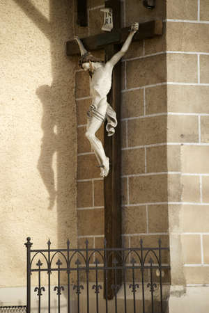 parish: Baden, Austria - November 15, 2015: A statue of Jesus on the cross casts a shadow on the wall of the Church of St. Stephan on November 15, 2015 in Baden near Vienna.