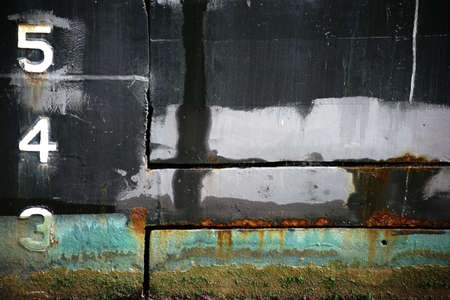 welds: The closeup of a rusty and with algae overgrown vessel wall of a tanker.