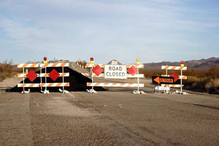 sign: A road barrier with warning lights and a tar pile on Route 66.