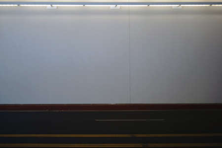 halogen lighting: The illuminated and homogeneous wall of an underpass with an adjacent road marking. Stock Photo