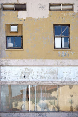 rundown: A run-down residential and commercial building with a faded facade and reflections in the windows.