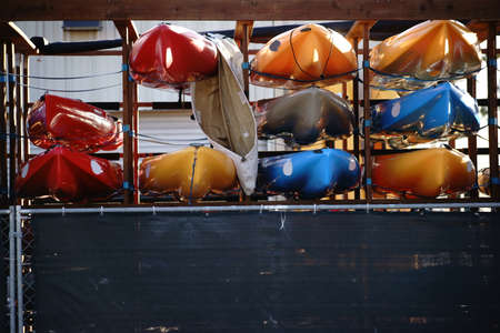 jacked: A series of canoes is stacked on a shelf of a boat rental company.