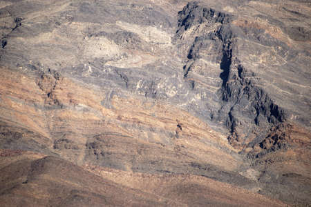 geological formation: The close-up of a mountain with different rock layers and distortions.