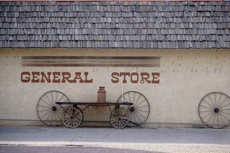 The facade of an old vintage store with old cart wheels.