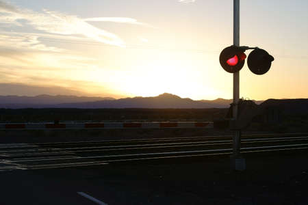 railroad crossing: A railroad crossing with red signal light in the evening during a sunset in the twilight.