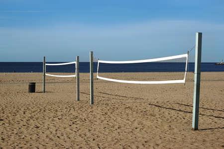 volleyball net: A beach volleyball court with volleyball net on the beach in Long Beach near the ocean.