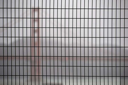 inclement weather: The Golden Gate Bridge in misty rain Weather blurred behind a fence. Stock Photo