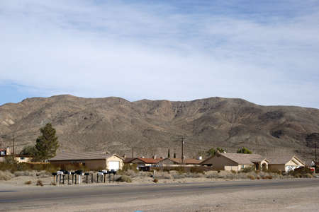 barstow: Family houses on a street in Barstow with a mountain range in the background. Stock Photo