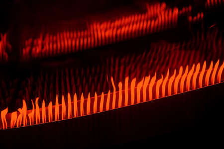 gas nozzle: A series of flames from the nozzle gas is reflected on the wall. Stock Photo