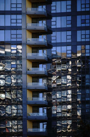 irregular shapes: Abstract reflections of surrounding buildings in the glass facade of a modern building.