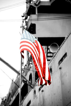 The American flag waves in front of a warship.
