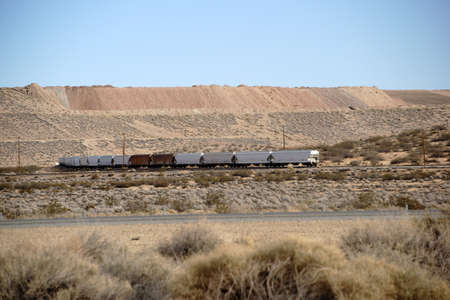A freight train crosses the Mojave desert with towering sand slopes. Stock Photo