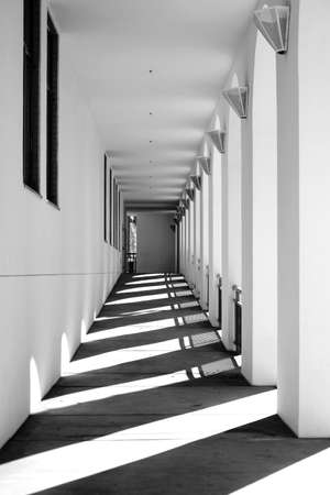 shadow: The columns and pillars of a narrow corridor cast shadows. Stock Photo