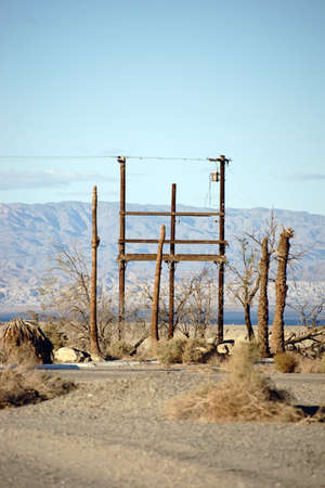 telephone pole: A radio mast and telephone pole standing in the desert at the Salton Sea in the ghost town of Salton City. Stock Photo