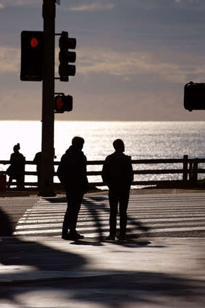 semaforo peatonal: Las siluetas de los peatones, que pasan por un sem�foro para ver el atardecer en la playa.