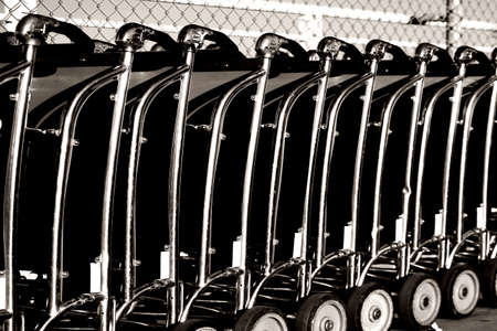 ranked: Baggage car of a luggage cart rental are consecutively ranked on the sidewalk and the entrance of an airport. Stock Photo