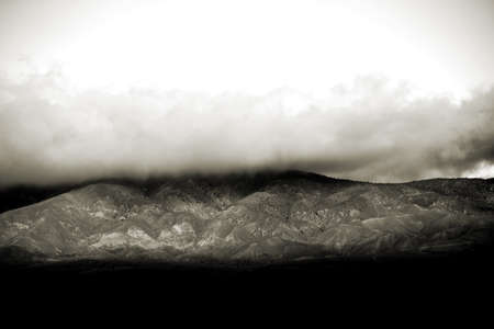 bernardino: Clouds and fog pull over the peaks and ridges of a mountain or a mountain range.