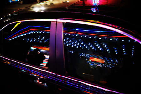 windows: A luxury car is on Hollywood Boulevard and reflects abstract lights.