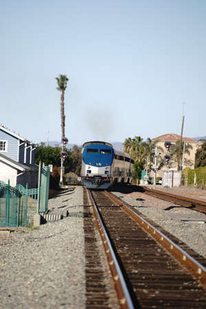 oceanside: A train runs on a track in Oceanside between houses.