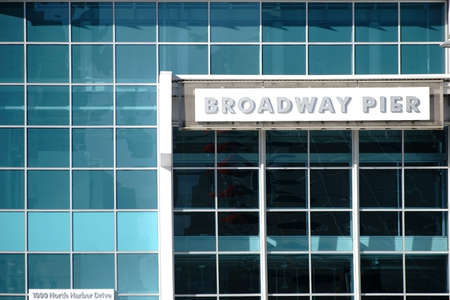 tinted glasses: San Diego, United States - December 25, 2015: The glass facade and the modern entrance with sign of the Broadway Pier on December 25, 2015 at the Port of San Diego.