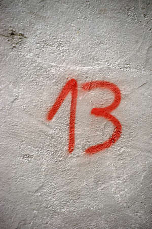 sprayed: The number 13 sprayed on the wall of a house. Stock Photo