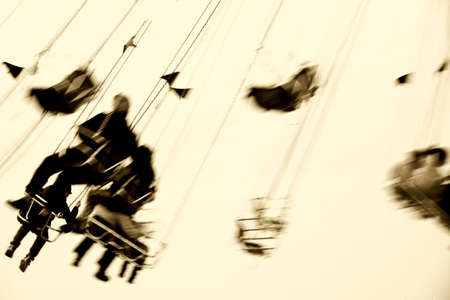 chain swing ride: The abstract silhouettes of sitting visitors on a rotating swing ride.