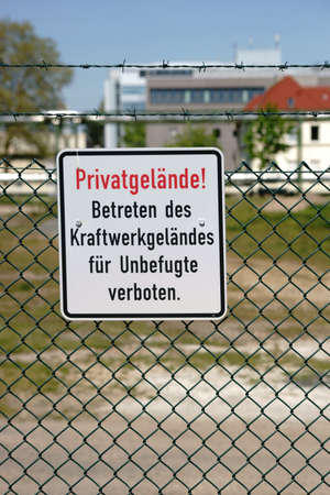 private property: The sign private property of a power plant on a barbed wire fence. Stock Photo