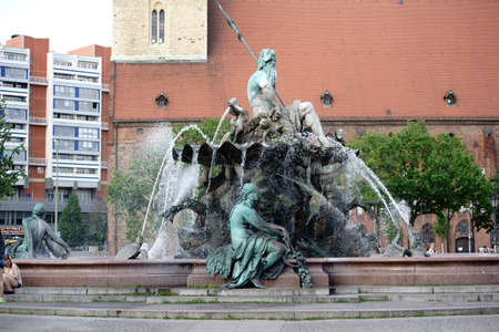 verdigris: Berlin, Germany - May 10, 2016: Pedestrians and young people sitting on the famous Neptune Fountain at the Alexander Place on May 10, 2016 in Berlin.