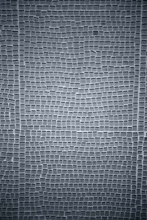 splinters: The close-up of a wall made of glass tiles splinters with a permeable surface.