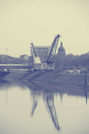 inland waterways: Two cranes are reflected in the river port of Mainz in the water.