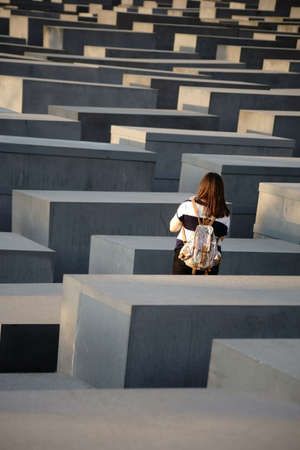 dreary: Berlin, Germany - May 10, 2016: A tourist stands between the gray concrete blocks of the Monument to the Murdered Jews of Europe on May 10, 2016 in Berlin. Editorial