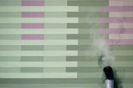 smoldering: The smoky chimney of an industrial plant on the outside wall of a power plant.