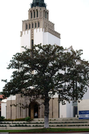 church flower: Los Angeles, United States - December 27, 2015: The entrance and tower of Westwood UMC church with a tree and flower beds in front of its white facade on December 27, 2015 in Los Angeles.