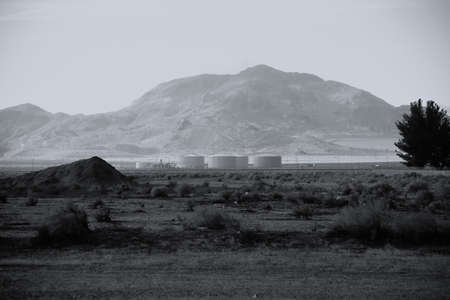 storage tanks: A dump with storage tanks and industrial buildings in the Mojave Desert. Stock Photo