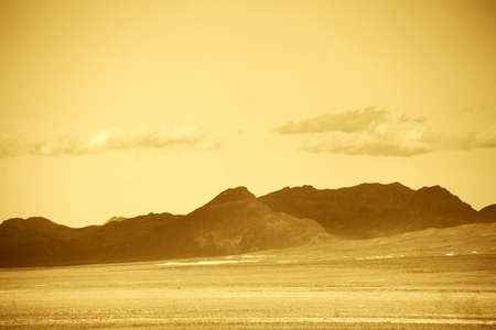 near death: A mountain range with dark layers of rock and faults near the Death Valley Junction. Stock Photo