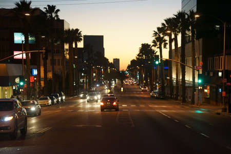 Santa Monica, USA - December 27, 2015: Traffic on Santa Monica Boulevard with illuminated shops, stores and restaurants during the sunset on December 27, 2015 in Santa Monica.