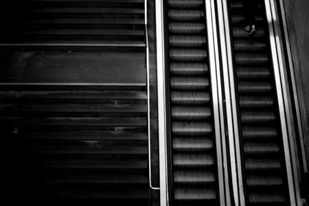 metallic stairs: The top view of a modern escalator next to a normal staircase.