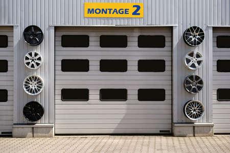 Hay un garaje con varios garajes y llantas deportivas para la decoración.