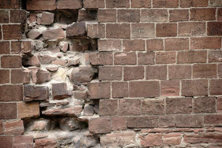 demarcation: A wall of distinctive red bricks with damage and holes. Stock Photo
