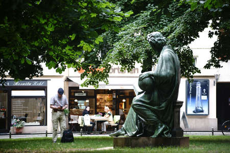allegory: Berlin, Germany - June 21, 2016: A tourist photographs the sculpture Allegory of Science by sculptor Albert Wolff at the Nikolai Church in the Nikolai quarter on  June 21, 2016 in Berlin.